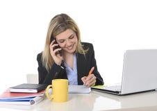 Glückliche kaukasische blonde arbeitende Unterhaltung der Geschäftsfrau am Handy am Bürocomputertisch Stockbilder