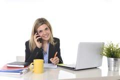 Glückliche kaukasische blonde arbeitende Unterhaltung der Geschäftsfrau am Handy am Bürocomputertisch Lizenzfreies Stockfoto
