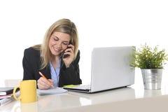 Glückliche kaukasische blonde arbeitende Unterhaltung der Geschäftsfrau am Handy am Bürocomputertisch Lizenzfreies Stockbild