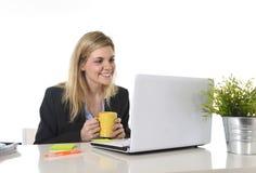 Glückliche kaukasische blonde Geschäftsfrau, die an Laptop-Computer am modernen Schreibtisch arbeitet Stockbild
