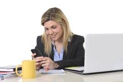 Glückliche kaukasische blonde Geschäftsfrau, die unter Verwendung des Handys am Bürocomputertisch arbeitet Stockfotografie