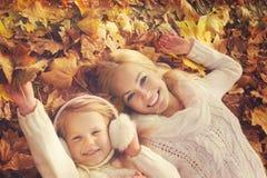 Glückliche kaukasische blonde Mutter und Tochter kleideten in den Weiß gestrickten Strickjacken an und lagen im gelben Herbstlaub Stockfoto