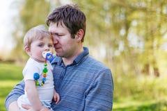 Glückliche kaukasische Familie von zwei: Andbaby Junge des jungen Vaters im sprin Lizenzfreies Stockbild