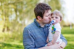 Glückliche kaukasische Familie von zwei: Andbaby Junge des jungen Vaters im sprin Lizenzfreie Stockfotografie