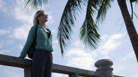 Glückliche kaukasische Frau mit dem langen blonden Haar in der Sonnenbrille und in grünem Hemd, die nahe Palme auf einem Blau ste stock video footage