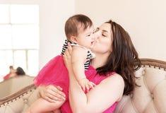 Glückliche kaukasische Mutter, die ihre Babytochter zu Hause sitzt auf dem Sofa küsst stockfoto