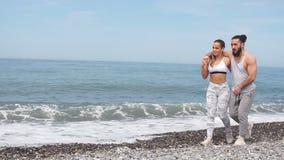Glückliche kaukasische sportive Paare, die zusammen auf einen Strand gehen stock video footage