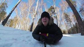 Glückliche Kerlfahrten und lächelndes snowtube auf schneebedeckte Straßen Langsame Bewegung Schneewinterlandschaft Draußen Sport stock video footage