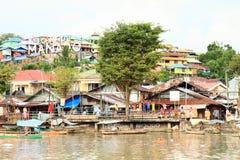 Glückliche Kinder auf Bank von Fluss in Manado Stockfotografie
