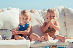 Glückliche Kinder auf dem Hintergrund des Meeres Lustige Kinder, die draußen spielen Reisenkoffer mit Meerblick nach innen Stockbild