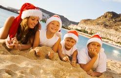 Glückliche Kinder auf dem Strand mit Weihnachtshüten Lizenzfreies Stockbild