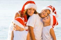 Glückliche Kinder auf dem Strand mit Weihnachtshüten Lizenzfreies Stockfoto