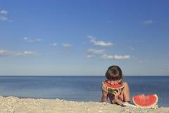 Glückliche Kinder auf dem Strand süße Wassermelone essend Stockfotos