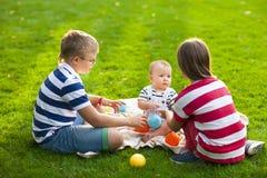 Glückliche Kinder auf grünem Gras im Sommer parken stolzer hübscher Gärtner stockfotos