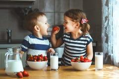 Glückliche Kinder Bruder und Schwester, die Erdbeeren mit Milch essen stockfotos