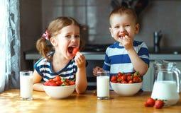Glückliche Kinder Bruder und Schwester, die Erdbeeren mit Milch essen stockfotografie