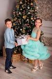 Glückliche Kinder Bruder und Schwester nahe dem Baum des neuen Jahres mit Weihnachtsgeschenk stockfoto