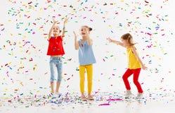 Glückliche Kinder an den Feiertagen, die an in mehrfarbige Konfettis springen lizenzfreie stockbilder