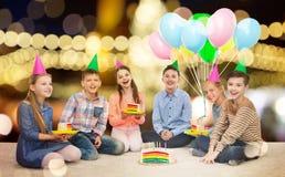 Glückliche Kinder in den Parteihüten mit Geburtstagskuchen stockfotos