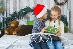 Glückliche Kinder, die auf Bett sitzen und Geschenke halten Stockfotos