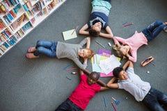 Glückliche Kinder, die auf Boden liegen lizenzfreie stockfotografie