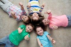 Glückliche Kinder, die auf Boden liegen und sich Daumen zeigen Stockfotografie