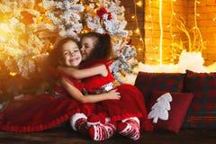 Glückliche Kinder, die auf dem Boden nahe einem Weihnachtsbaum und einem a sitzen lizenzfreie stockbilder