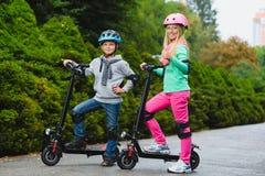 Glückliche Kinder, die auf dem elektrischen Roller im Freien stehen Stockfotografie