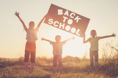 Glückliche Kinder, die auf dem Feld zur Sonnenuntergangzeit spielen Stockfotos