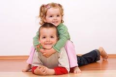 Glückliche Kinder, die auf dem Fußboden spielen Stockfotos