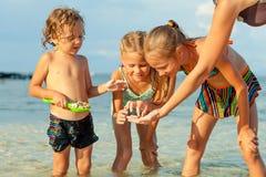 Glückliche Kinder, die auf dem Strand spielen Stockbilder