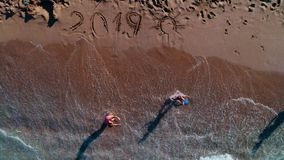 Glückliche Kinder, die auf dem Strand spielen Neues Jahr 2019 geschrieben auf den Sand