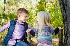 Glückliche Kinder, die auf dem Zaun Facing Each Other sitzen lizenzfreie stockbilder