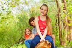 Glückliche Kinder, die auf einer Anmeldungsreihe sitzen Stockfotografie