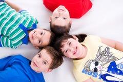 Glückliche Kinder, die auf Fußboden liegen Stockbilder