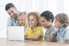 Glückliche Kinder, die auf Laptop programmieren lizenzfreie stockfotos