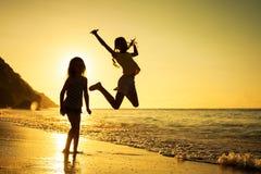 Glückliche Kinder, die auf Strand spielen Lizenzfreies Stockfoto