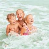 Glückliche Kinder, die auf Strand spielen Stockfoto
