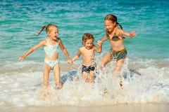 Glückliche Kinder, die auf Strand spielen Stockbilder