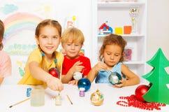 Glückliche Kinder, die Bälle des neuen Jahres für Weihnachtsbaum malen Stockfotos