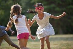 Glückliche Kinder, die Blinder ` s Büffelleder spielen Stockfoto