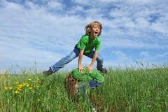 Glückliche Kinder, die Bockspringen spielen Stockbild