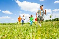 Glückliche Kinder, die in das Feld spielen und laufen Stockfoto