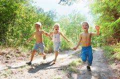 Glückliche Kinder, die in das Holz laufen Stockfoto