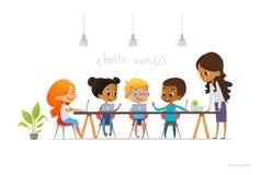 Glückliche Kinder, die an den Laptops sitzen und die Programmierung während der Schullektion, lächelnder Lehrer steht nahe ihnen  Stockbilder