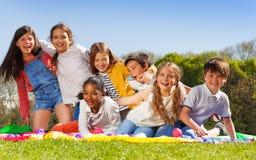 Glückliche Kinder, die den Spaß sitzt auf dem Rasen im Park haben stockfoto