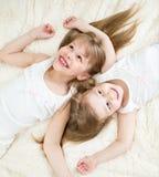 Glückliche Kinder, die in der Draufsicht der Pyjamas liegen stockbild