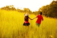 Glückliche Kinder, die an der Wiese laufen Stockbilder