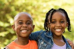 Glückliche Kinder, die die Kamera lächeln und betrachten Stockfotografie