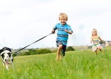 Glückliche Kinder, die draußen mit Hund laufen Stockfotos